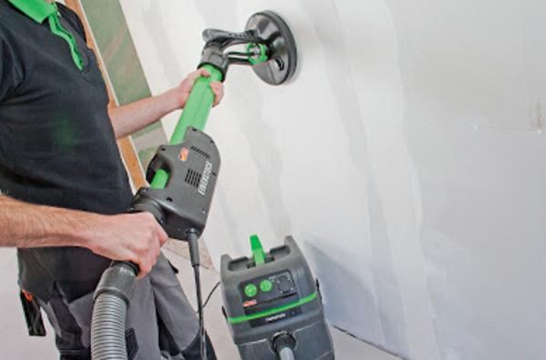 Dùng máy chà nhám để làm mịn bề mặt tường